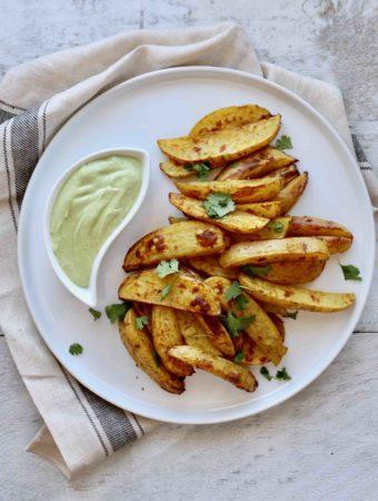 Quartiers de pommes de terre rôties au cari et trempette à la lime et à la coriandre